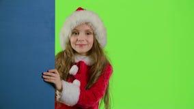 Muchacha del niño que mira a escondidas hacia fuera de detrás el tablero azul Pantalla verde metrajes