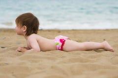 Muchacha del niño que pone en la playa de la arena Fotografía de archivo