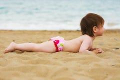 Muchacha del niño que pone en la playa de la arena Fotos de archivo