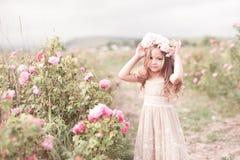 Muchacha del niño que presenta en rosaleda Imagen de archivo