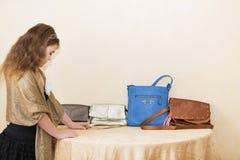 Muchacha del niño que se coloca cerca el tabla y que elige los diversos monederos de cuero de moda elegantes de las señoras Fotografía de archivo