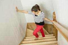 Muchacha del niño que se coloca en la escalera en casa Imagen de archivo