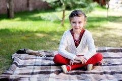 Muchacha del niño que se sienta en la tela escocesa en un jardín Imagenes de archivo