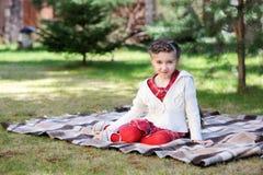 Muchacha del niño que se sienta en la tela escocesa en un jardín Imagen de archivo libre de regalías