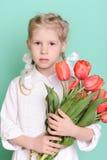 Muchacha del niño que sostiene tulipanes rojos Imágenes de archivo libres de regalías