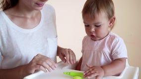 Muchacha del niño y madre o canguro que juega el juguete colorido de la arcilla almacen de video