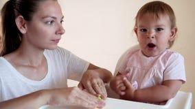 Muchacha del niño y madre o canguro que juega el juguete colorido de la arcilla almacen de metraje de vídeo