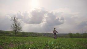 Muchacha del ni?o en una bici en el campo en el tiempo de la puesta del sol, concepto de la forma de vida metrajes