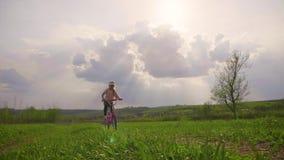 Muchacha del ni?o en una bici en el campo en el tiempo de la puesta del sol, concepto de la forma de vida almacen de video
