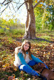 Muchacha del niño del otoño con el perro casero relajado en bosque de la caída Imagen de archivo libre de regalías