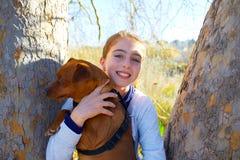 Muchacha del niño del otoño con el perro casero relajado en bosque de la caída Imagenes de archivo