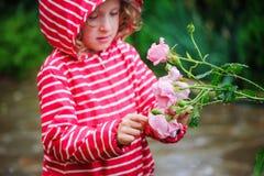 Muchacha del niño en el impermeable rayado rojo que juega con las rosas mojadas en jardín lluvioso del verano Concepto del cuidad Imagen de archivo