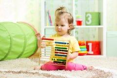Muchacha del niño que juega con el ábaco, aprendiendo temprano Foto de archivo