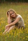Muchacha del país que se sienta en la hierba Fotos de archivo libres de regalías