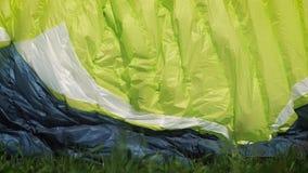 Muchacha del Paragliding El ala flexible está lista para sacar sobre una colina verde almacen de metraje de vídeo