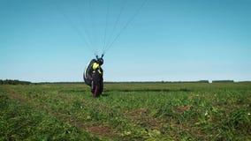 Muchacha del Paragliding El ala flexible está lista para sacar sobre una colina verde metrajes