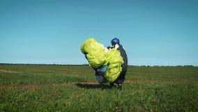 Muchacha del Paragliding El ala flexible está lista para sacar sobre una colina verde lleva un paracaídas después de aterrizar metrajes