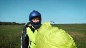 Muchacha del Paragliding El ala flexible está lista para sacar sobre una colina verde lleva un paracaídas después de aterrizar almacen de video