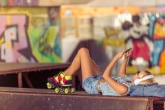 Muchacha del patinador del rodillo con el artilugio Imagen de archivo libre de regalías