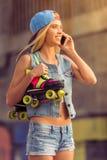 Muchacha del patinador del rodillo con el artilugio Fotografía de archivo libre de regalías