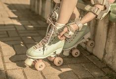 Muchacha del patinador que pone en los pcteres de ruedas retros de la menta al aire libre Foto de archivo libre de regalías