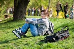 Muchacha del patinador que se reclina en el parque Imagenes de archivo