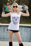 Muchacha del patinador que sostiene el monopatín Imagen de archivo