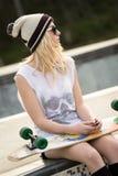 Muchacha del patinador que sostiene el monopatín Fotos de archivo libres de regalías