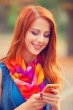 Muchacha del pelirrojo con el teléfono móvil Imagenes de archivo