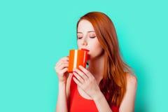Muchacha del pelirrojo con la taza coralina de café o de té Fotografía de archivo