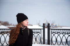 Muchacha del pelirrojo en capa negra en un día soleado Fotografía de archivo