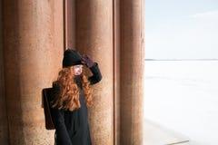 Muchacha del pelirrojo en capa negra en un día soleado Foto de archivo