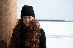 Muchacha del pelirrojo en capa negra en un día soleado Fotos de archivo