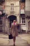 Muchacha del pelirrojo en la yarda con la maleta en Odessa. Fotografía de archivo