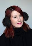 Muchacha del pelirrojo en manguitos del oído de la piel Fotografía de archivo libre de regalías