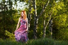 Muchacha del pelirrojo que camina bajo rayos del bosque de la puesta del sol Imagen de archivo libre de regalías