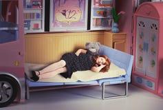 Muchacha del pelirrojo que duerme en una cama de la muñeca Foto de archivo libre de regalías