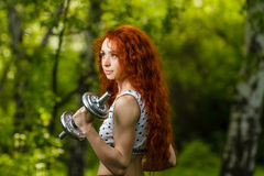 Muchacha del pelirrojo que ejercita con pesas de gimnasia en el bosque Imagen de archivo libre de regalías