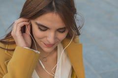 Muchacha del pelirrojo que escucha la música en las calles de la ciudad Imágenes de archivo libres de regalías