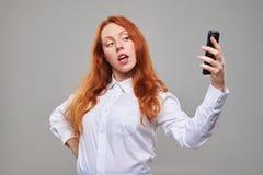 Muchacha del pelirrojo que hace el selfie contra fondo gris Imágenes de archivo libres de regalías