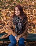 Muchacha del pelirrojo que se sienta en banco en libro del parque y de lectura Imagen de archivo