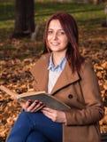 Muchacha del pelirrojo que se sienta en banco en libro del parque y de lectura Imagen de archivo libre de regalías