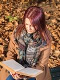 Muchacha del pelirrojo que se sienta en banco en parque Imagen de archivo libre de regalías