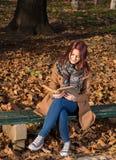 Muchacha del pelirrojo que se sienta en banco en parque Imágenes de archivo libres de regalías