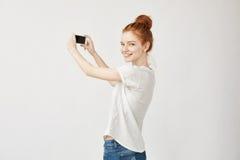 Muchacha del pelirrojo que sostiene el teléfono que se coloca detrás de mirada a la cámara Imagen de archivo