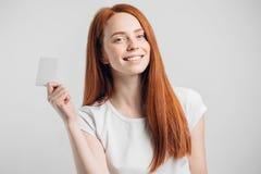 Muchacha del pelirrojo que sostiene la tarjeta de crédito y que sonríe en el fondo blanco Fotos de archivo libres de regalías