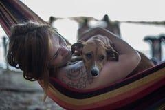 Muchacha del pelirrojo y su perro que mienten en un salón en la playa en verano Foto de archivo