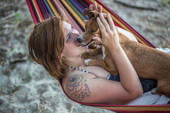 Muchacha del pelirrojo y su perro que mienten en un salón en la playa en verano Imagenes de archivo