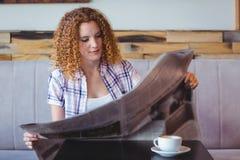 Muchacha del pelo bastante rizado que come la taza de café y que lee el periódico Fotos de archivo