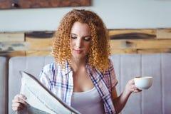 Muchacha del pelo bastante rizado que come la taza de café y que lee el periódico Imagenes de archivo